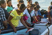 Puerto Escondido beach, Oaxaca, Mexico, customers arriving at dawn to buy fresly caught fish from the crews of small fishing boats - Jim West - 04-02-2020