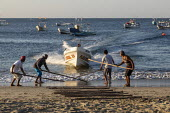 Puerto Escondido beach, Oaxaca, Mexico, Fishing boats arriving at dawn to sell fresly caught fish. The captain steers the boat at full speed towards the beach while the crew lays down sticks to create... - Jim West - 04-02-2020