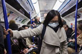Passenger with face mask, London Underground - Duncan Phillips - 2020,2020s,adult,adults,Asian,Asians,BAME,BAMEs,Black,BME,bmes,carriage,carriages,cities,City,COMMUTE,commuter,commuters,commuting,contagious,coronavirus,Covid 19,crisis,crowd,crowded,disease,DISEASES