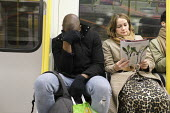 Passenger covering his face, London Underground - Duncan Phillips - 2020,2020s,adult,adults,BAME,BAMEs,Black,BME,bmes,carriage,carriages,cities,City,COMMUTE,commuter,commuters,commuting,contagious,coronavirus,Covid 19,crisis,crowd,crowded,disease,DISEASES,diversity,ep