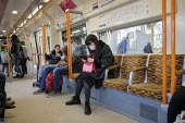 Passenger wearing a face mask, London Overground train - Philip Wolmuth - Health,2020,2020s,Asian,Asians,BAME,BAMEs,Black,BME,bmes,cities,city,contagion,contagious,coronavirus,Covid 19,covid-19,crisis,disease,DISEASES,diversity,epidemic,ethnic,ethnicity,face,face mask,face