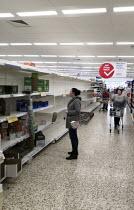 Empty shelves due to panic buying, Tesco, Bristol. - Sam Morgan Moore - 2020,2020s,bought,buy,buyer,buyers,buying,commodities,commodity,communicating,communication,consumer,consumers,contagion,contagious,Coronavirus,Covid 19,COVID-19,crisis,customer,customers,demand,disea