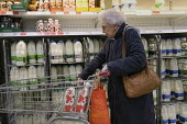 Elderly shopper buying milk, Sainsburys imposes new shopping rules for the elderly amid coronavirus panic buying, Putney, London - Duncan Phillips - 17-03-2020