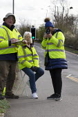 Community Speedwatch group measuring vehicle speed in a 30 mph speed limit. Trained volunteers from the local community monitoring the speeds of vehicles with approved, hand held speed measurement dev... - John Harris - 2020,2020s,adult,adults,age,ageing population,AUTO,AUTOMOBILE,AUTOMOBILES,car,cars,CLJ,communicating,communication,communities,Community,Community Speedwatch group,device,devices,elderly,encouraging,F