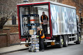 Workers unloading drinks from a delivery lorry, Stratford upon Avon, Warwickshire. Matthew Clark drinks distributor supplying alcohol products - John Harris - 2020,2020s,alcohol,carries,carry,carrying,cart,carts,deliveries,delivering,delivery,distributing,distribution,drink,drinks,driver,drivers,DRIVING,EBF,Economic,Economy,employee,employees,Employment,HAU