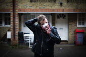 Young man wearing a face mask, Kilburn, London - Connor Matheson - 2020,2020s,apparel,clothing,coronavirus,covid-19,crisis,disease,DISEASES,epidemic,face,face mask,face masks,FACES,hazard,hazardous,hazards,HEA,Health,Health and Safety,home,homes,Housing Estate,hygien
