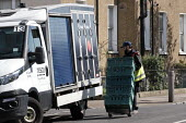 Tesco supermarket food shopping van driver making a delivery, Putney, London - Duncan Phillips - 2020,2020s,Asian,Asians,BAME,BAMEs,Black,BME,bmes,cart,carts,cities,City,coronavirus,covid-19,deliveries,delivering,delivery,disease,DISEASES,diversity,driver,drivers,DRIVING,EARNINGS,EBF,Economic,Eco