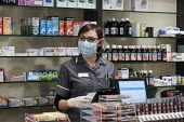 Coronavirus pandemic. Pharmacists working in facemasks and disposible gloves, pharmacy, Putney, London - Duncan Phillips - 2020,2020s,buy,buyer,buyers,buying,cities,City,coronavirus,covid-19,crisis,disease,DISEASES,drug,drugs,EBF,Economic,Economy,employee,employees,Employment,epidemic,face mask,face masks,FEMALE,gloves,ha