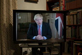 Boris Johnson speaking to the nation on TV, announcing Strict new curbs on life in the UK to tackle the spread of coronavirus - John Harris - 2020,2020s,Boris Johnson,communicating,communication,CONSERVATIVE,Conservative Party,conservatives,coronavirus,covid-19,disease,DISEASES,epidemic,flag,flags,HEA,Health,home,homes,male,man,men,MP,MPs,p
