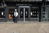 Bank worker guarding the door with hazard tape on the floor to try and maintain social distance, restricting customers to two at a time, Coventry Building Society, Stratford Upon Avon, Warwickshire - John Harris - 26-03-2020