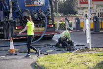 Emergency tank cleaning, Shell petrol station Stratford Upon Avon, Warwickshire. Jogger exercising - John Harris - 27-03-2020