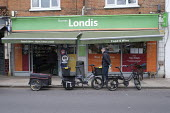 Coronavirus pandemic, electric bike delivery service set up by local independent shops to deliver food and vital supplies, Barnes, London - Duncan Phillips - 2020,2020s,bicycle,bicycles,BICYCLING,Bicyclist,Bicyclists,bike,bikes,Bosch eBike,buy,buyer,buyers,buying,cities,City,coronavirus,covid-19,cycle,cycles,cycling,Cyclist,Cyclists,deliver,deliveries,deli