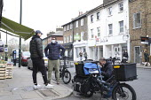 Coronavirus pandemic, electric bike delivery service set up by local independent shops to deliver food and vital supplies, Barnes, London - Duncan Phillips - 30-03-2020