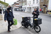 Coronavirus pandemic, electric bike delivery service set up by local independent shops to deliver food and vital supplies, Barnes, London - Duncan Phillips - 2020,2020s,bicycle,bicycles,BICYCLING,Bicyclist,Bicyclists,bike,bikes,bought,buy,buyer,buyers,buying,cities,City,consumer,consumers,coronavirus,covid-19,customer,customers,cycle,cycles,cycling,Cyclist