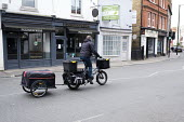 Coronavirus pandemic, electric bike delivery service set up by local independent shops to deliver food and vital supplies, Barnes, London - Duncan Phillips - 2020,2020s,bicycle,bicycles,BICYCLING,Bicyclist,Bicyclists,bike,bikes,buy,buyer,buyers,buying,cities,City,coronavirus,covid-19,cycle,cycles,cycling,Cyclist,Cyclists,deliver,deliveries,delivering,deliv