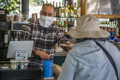 California, USA. Barista serving at a cafe wearing a mask made from a paper towel. He works in an essential job - David Bacon - 2020,2020s,America,barista,cafe,cafes,California,cash register,catering,cities,City,coffee,coronavirus,covid-19,customer,customers,disease,DISEASES,EARNINGS,EBF,Economic,Economy,employee,employees,Emp