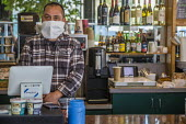 California, USA. Barista serving at a cafe wearing a mask made from a paper towel. He works in an essential job - David Bacon - 2020,2020s,America,barista,cafe,cafes,California,cash register,catering,cities,City,coffee,coronavirus,covid-19,disease,DISEASES,EARNINGS,EBF,Economic,Economy,employee,employees,Employment,epidemic,es