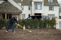 Coronavirus Pandemic. Gardener raking a new lawn outside a mansion, Stratford Upon Avon, Warwickshire - John Harris - 2020,2020s,AFFLUENCE,AFFLUENT,Bourgeoisie,coronavirus,covid-19,disease,DISEASES,EARNINGS,elite,elitism,employee,employees,Employment,epidemic,EQUALITY,garden,gardener,gardeners,gardening,gardens,HEA,H