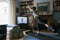 Coronavirus Pandemic. Pilates trainer giving a lesson over the internet. Woman exercising at home, Stratford Upon Avon, Warwickshire - John Harris - 02-04-2020