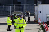 Testing NHS workers for Covid-19, Drive thru Coronavirus test centre, Edgbaston Cricket Ground car park, Birmingham. Swab sample being take from the back of the throat. Security guards attempting to p... - John Harris - 07-04-2020