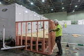 Detroit, Michigan USA. Emergency field hospital under construction, TCF convention center. The 1,000-bed hospital will care for Covid-19 patients. A carpenter working on a shower facility. - Jim West - 06-04-2020