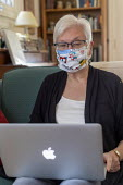 Detroit, Michigan USA. Coronavirus Pandemic. Susan Newell 71 wearing a homemake face mask whilst taking part of a Zoom meeting online - Jim West - 2020,2020s,age,ageing population,America,american,americans,apple mac,apple macs,bluetooth,cities,City,communicating,communication,communications,COMPUTE,computer,computers,COMPUTING,desktop,Detroit,d