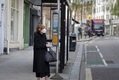 Coronavirus pandemic. Woman wearing a face mask and disposable gloves, bus stop, West Hampstead, London - Philip Wolmuth - 2020,2020s,bus,bus service,Bus Stop,buses,cities,City,Coronavirus pandemic,Covid-19,desease,disease,DISEASES,face,face mask,face masks,FACES,FEMALE,gloves,HEA,Health,holiday,holidays,infection,infecti