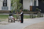 Coronavirus pandemic, Police Officers patrolling parks to enforce social distancing and compliance to lockdown restrictions, Barnes, London - Duncan Phillips - 2020,2020s,activities,adult,adults,BAME,BAMEs,bench,Black,BME,bmes,child,CHILDHOOD,children,cities,City,CLJ,communicating,communication,conversation,conversations,coronavirus,covid-19,dialogue,discour