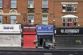 Coronavirus pandemic. Woman shopping walking past closed shops and businesses, Kilburn, London - Philip Wolmuth - 22-04-2020