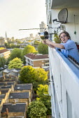 Coronavirus Pandemic. Clap for our Carers, Helen banging a saucepan, tower block, Tower Hamlets, East London - Jess Hurd - 14-05-2020