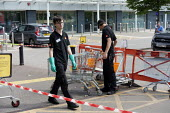Coronavirus Pandemic: B&Q store, young shopworkers cleaning trollies, Stratford upon Avon - John Harris - 23-05-2020