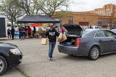 Detroit, Michigan, USA: Volunteers distributing free food in a poor neighborhood during the coronavirus pandemic - Jim West - 2020,2020s,African American,African Americans,African-American,America,american,americans,AUTO,AUTOMOBILE,AUTOMOBILES,BAME,BAMEs,black,Black and White,BME,bmes,car,cars,charitable,charity,cities,City,