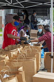 Detroit, Michigan, USA: Volunteers distributing free food in a poor neighborhood during the coronavirus pandemic - Jim West - 2020,2020s,African American,African Americans,African-American,America,american,americans,BAME,BAMEs,black,Black and White,BME,bmes,charitable,charity,cities,City,coronavirus,covid-19,Detroit,disease,