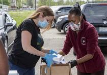 Detroit, Michigan, USA: Volunteers distributing free food in a poor neighborhood during the coronavirus pandemic - Jim West - 2020,2020s,African American,African Americans,America,american,americans,BAME,BAMEs,black,Black and White,BME,bmes,charitable,charity,cities,City,coronavirus,covid-19,Detroit,disease,DISEASES,distribu