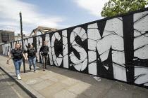 Plain clothes police unit walk past United Aganst Racism graffitii, Brick Lane, East London - Jess Hurd - 09-06-2020