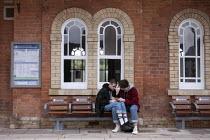 Coronavirus Pandemic. Lovers sitting on seats maked Do Not Sit Here, Stratford upon Avon Railway Station - John Harris - 11-06-2020