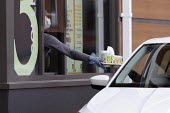 Coronavirus Pandemic. McDonald's reopening drive thru at all UK restaurants. Worker serving with face mask and screens, Stratford Upon Avon - John Harris - 04-06-2020