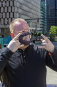 Detroit, Michigan. USA Protestor speaking in sign language before a Black Disabled Lives Matter protest. His face mask has a transparent panel which allows deaf persons to read his lips. - Jim West - 15-06-2020