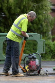Workers tarmacing after installing a new gas main, using a plate compactor without ear defenders, Stratford-upon Avon - John Harris - 19-06-2020