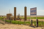 Colorado, USA. Support Your Local Rnacher Buy U.S.A. Beef sign. Farm silos and oil storage tanks. Oil development has allowed many family farms to continue operating. But that oil boom is now threaten... - Jim West - 03-07-2020