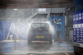 Migrant workers spray cleaning a car, Car Wash, Stratford Upon Avon - John Harris - 29-07-2020