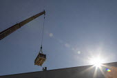 Denver, USA: Workers installing solar panels on the roof of new affordable housing building. Lifting equipment for a solar energy installation to the top of a new affordable housing building. The sola... - Jim West - 02-07-2020