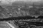 Nantymoel cemetery, Wyndham Western Mine, 1972, Ogmore Vale, South Wales coalfield. A lone figure walks past Nantymoel cemetery, which is overshadowed by the pit. Many of those buried there will have... - Martin Mayer - 15-01-1972