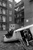Children playing in a wrecked car, Chaucer House, 1972, a slum housing block, Southwark, South London 1972. Chaucer House is a Council run half-way house for homeless families - Martin Mayer - 23-02-1972