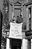 Group of young squatters, Elgin Avenue 1975 looking on as the bailiffs and the removals vans move in. West London. Banners: Homes For All, Reverse Cuts in Housing - Martin Mayer - 15-10-1975