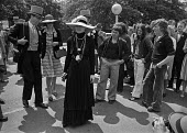 Royal Ascot races 1975 striking stable lads from Newmarket handing out leaflets to racegoers arriving in top hats and morning dress. The strikers look on bemused at a celebrity posing for photographs.... - Martin Mayer - 16-06-1975