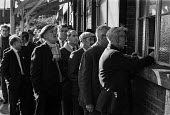 Miners collecting their pay 1970, Tilmonstone Colliery, Kent coalfield. Queuing to collect their wage packets from a payment window - Martin Mayer - 12-11-1970