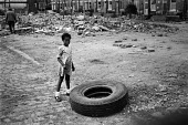 Black girl with a tyre in the rubble of Belfast, 1981 - NLA - 30-07-1981