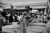 Notting Hill Carnival 1978. Steel band performing on the back of a lorry moving slowly through the streets, woman playing steel drums - Peter Arkell - 26-08-1978