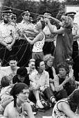 Women blockading RAF Greenham Common 1982, USAF airbase, Newbury, Berkshire. Women weave thread onto the gates of the main entrance, while others blockade it by sitting down. - Peter Arkell - 04-07-1983